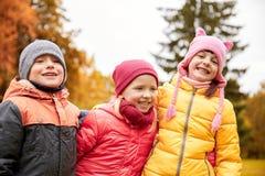 拥抱在秋天公园的小组愉快的孩子 免版税库存照片