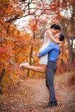 拥抱在秋天公园的微笑的夫妇 愉快的新娘和新郎在森林里,户外 免版税库存图片