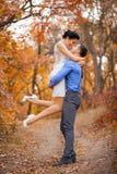 拥抱在秋天公园的愉快的夫妇 微笑的新娘和新郎在森林里,户外 免版税库存图片