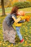 拥抱在秋天公园的愉快的母亲和儿童男孩 库存图片
