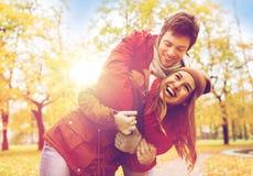 拥抱在秋天公园的愉快的年轻夫妇 免版税库存照片