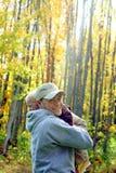 拥抱在秋天森林里的父亲和儿子 免版税库存图片