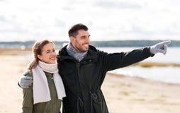 拥抱在秋天海滩的微笑的夫妇 免版税库存照片