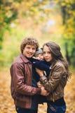 拥抱在秋天的年轻家庭在公园 免版税库存图片
