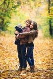拥抱在秋天的年轻愉快的家庭在公园 免版税图库摄影