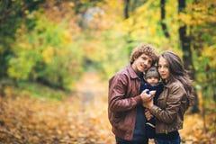 拥抱在秋天的年轻愉快的家庭在公园 图库摄影