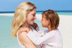 拥抱在美丽的海滩的母亲和女儿 免版税库存照片