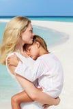 拥抱在美丽的海滩的母亲和女儿 图库摄影
