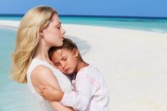 拥抱在美丽的海滩的母亲和女儿 免版税库存图片