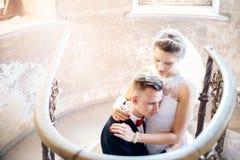 拥抱在老台阶附近的新婚佳偶 衣物夫妇日愉快的葡萄酒婚礼 库存照片