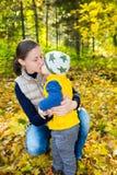 拥抱在自然的愉快的妈妈和儿童男孩在秋天 免版税库存照片