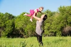 拥抱在自然童年和家庭的概念愉快的妈妈和儿童女孩 图库摄影