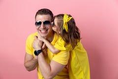 拥抱在色的桃红色背景的逗人喜爱的爸爸和女儿以黄色和太阳镜 背景概念框架沙子贝壳夏天 免版税库存照片