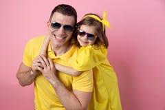 拥抱在色的桃红色背景的逗人喜爱的爸爸和女儿以黄色和太阳镜 背景概念框架沙子贝壳夏天 免版税图库摄影