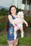 拥抱在花的愉快的妈妈和儿童女孩。户外美丽的母亲和她的婴孩 免版税库存图片