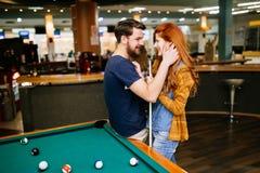拥抱在落袋撞球酒吧的夫妇 库存图片