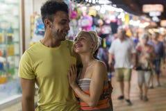 拥抱在街市,混合种族人和妇女愉快微笑上的夫妇看彼此 免版税库存照片