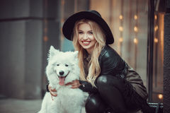 拥抱在街道上一条大狗的美丽,时髦地加工好的女孩 库存照片