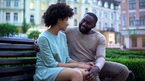 拥抱在长凳的年轻非洲夫妇在日落,日期在城市公园,严紧 免版税库存图片