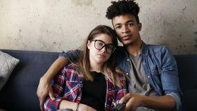 拥抱在长沙发的年轻行家逗人喜爱的愉快的夫妇,设法发现一个完善的电视频道 业余时间,享用 股票视频