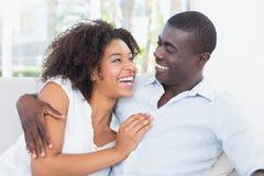 拥抱在长沙发的有吸引力的夫妇 免版税图库摄影