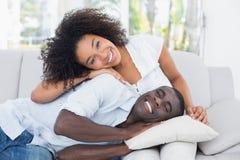 拥抱在长沙发的有吸引力的夫妇 免版税库存图片