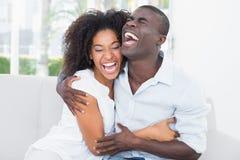 拥抱在长沙发的有吸引力的夫妇 图库摄影