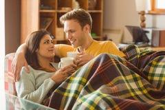 拥抱在长沙发的年轻夫妇在毯子下 库存图片