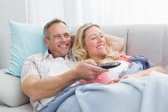 拥抱在长沙发观看的电视上的愉快的夫妇 免版税库存照片