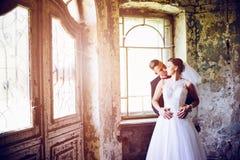 拥抱在门的新婚佳偶在一个老房子里 免版税库存照片