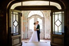 拥抱在门的新婚佳偶在一个老房子里 免版税库存图片
