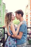 拥抱在阳台的美好的异性爱夫妇 背景的多彩多姿的都市房子 免版税库存照片