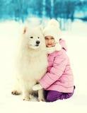 拥抱在雪的小孩白色萨莫耶特人狗在冬天 库存图片