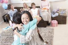 拥抱在婴儿送礼会的妇女 图库摄影