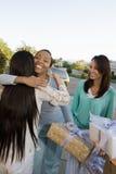 拥抱在婴儿送礼会的朋友 免版税库存照片