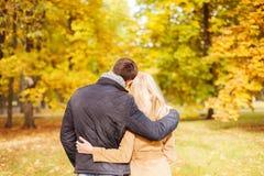 拥抱在从后面的秋天公园的夫妇 免版税库存照片