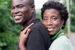 拥抱在绿色背景的愉快的年轻夫妇 免版税图库摄影