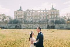 拥抱在绿色晴朗的草坪的有吸引力的新婚佳偶夫妇在美丽的被破坏的巴洛克式的宫殿附近 爱恋的新郎藏品 库存图片