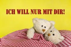 拥抱在chechered床上的两个米黄玩具熊。 免版税库存照片