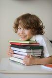 拥抱堆书的男小学生 图库摄影