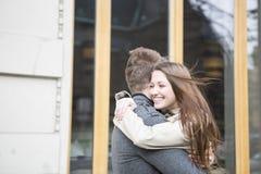 拥抱外部咖啡馆的浪漫夫妇侧视图  免版税库存照片
