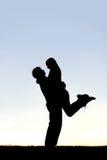 拥抱外面在日落的愉快的年轻夫妇剪影  免版税图库摄影