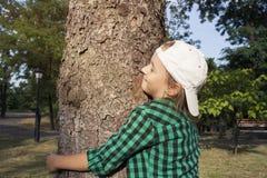 拥抱大树的愉快的美丽的女孩在公园 爱恋的本质 库存照片