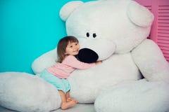 拥抱大白色玩具熊的美丽的小女孩 免版税库存图片
