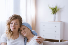 拥抱女儿的有希望的癌症妇女 库存照片