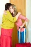 拥抱女儿的母亲在门附近 免版税库存照片