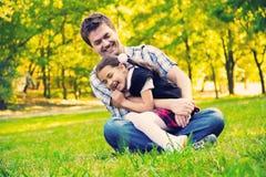 拥抱女儿的父亲在公园 免版税图库摄影