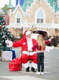 拥抱女孩的圣诞老人 库存图片