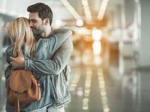 拥抱女性室内的高兴的男性 免版税库存图片