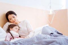 拥抱她不适的睡觉的孩子的爱恋的母亲 免版税库存图片